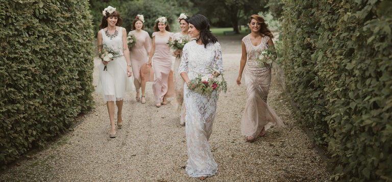 Lace bride walking with pastel bridesmaids
